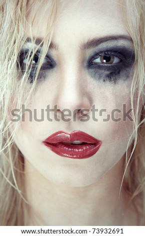 Crazy sad lady with bizarre dirty makeup. Close-up portrait - stock photo