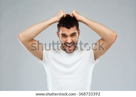 crazy shouting man in t-shirt over gray background - stock photo