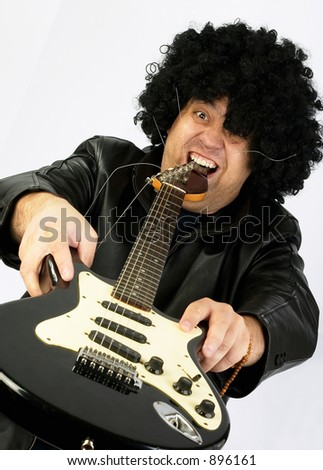 Crazy virtuoso. Excited rock guitarist swallowing an electric guitar ;o) - stock photo
