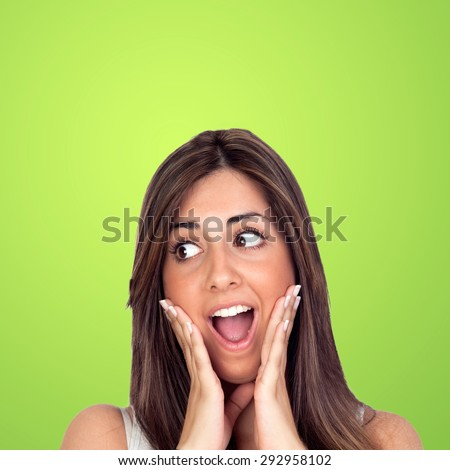 Crazy woman surprised on a green background - stock photo