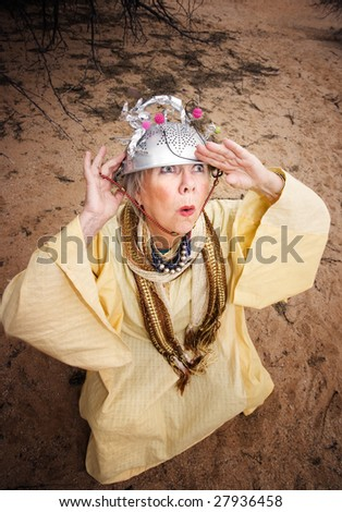 Crazy woman wearing a colander helmet waiting for a spaceship - stock photo