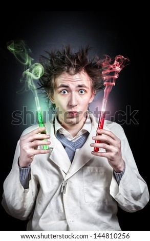 Crazy young doctor holding two test tubes with red and green liquid at black background - stock photo