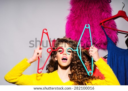 Crazy young girl with curly hair in yellow sweater holding hangers standing amid colorful clothes pink red blue colors on grey wall background, horizontal picture - stock photo