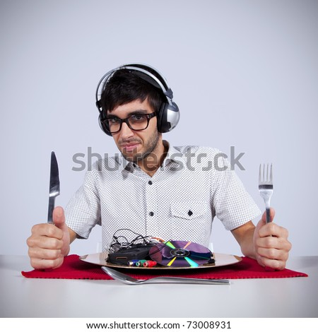 Crazy young man eating music at his dinner plate - stock photo