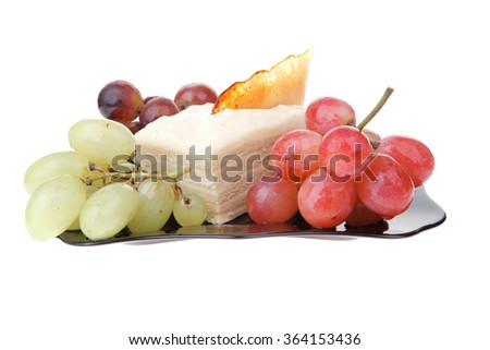 cream cake and grapes on black plate - stock photo