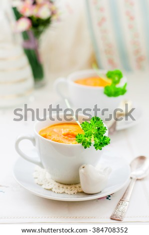 Cream Carrot Soup in a White Cup Garnished with a Parsley Leaf, copy space for your text - stock photo