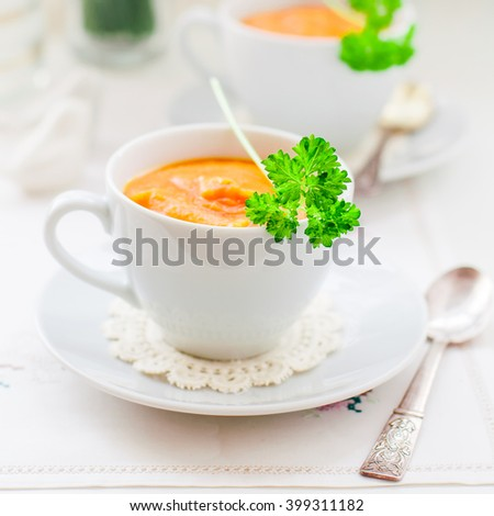 Cream Carrot Soup in a White Cup Garnished with a Parsley Leaf, square - stock photo