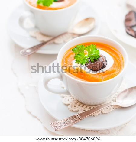 Cream Carrot Soup in a White Cup Garnished with Sour Cream, Truffle Slices and a Parsley Leaf, square - stock photo