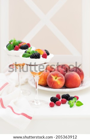 Cream cheese, biscuits, peaches and fresh berries dessert, selective focus - stock photo