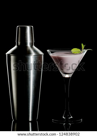 Cream cocktail with mint and  metal shaker on a black background