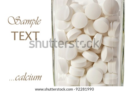 Cream colored nutritional supplements (calcium with magnesium and vitamin d) in glass bottle on white background with copy space. - stock photo