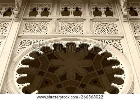Cream colored walls, wooden buildings, a beautiful carving. - stock photo