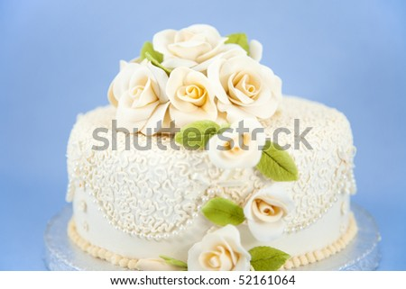 Cream colored wedding cake with floral decorations - stock photo
