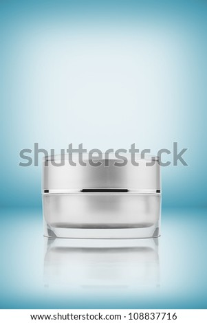 cream container on blue background - stock photo