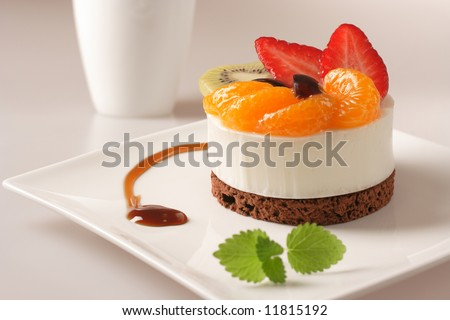 Cream dessert with fruit on white plate - stock photo