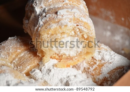 Cream filled pastries covered in powdered sugar in a a brown box.