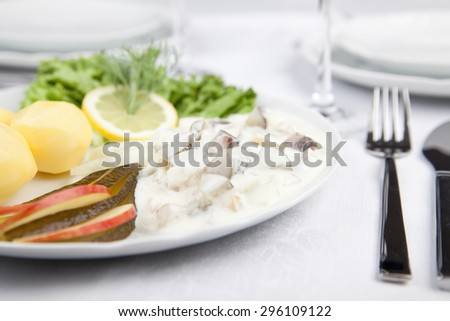 Cream herring with cucumbers, potatoes and salad - stock photo