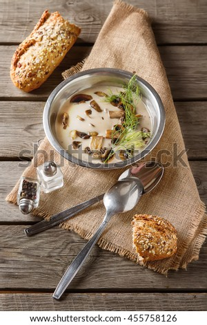 Cream homemade mushroom soup in the gray plate with parsley, wooden background. 