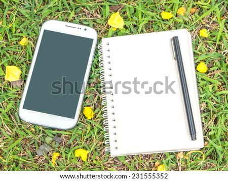 cream notebook with pen and mobile phone on green grass background. - stock photo