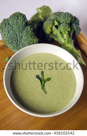 cream of broccoli soup in a white bowl on a wooden table with slices of the stems - stock photo