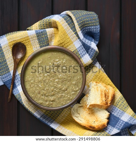 Cream of lentil soup in rustic bowl with wooden spoon and toasted bread slices on kitchen towel, photographed overhead on dark wood with natural light