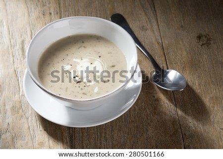 Cream of mushroom soup on a wooden table. Rustic and wholesome food. - stock photo
