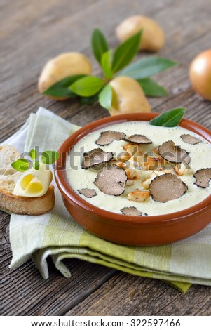 Cream of potato soup with delicious sliced black autumn truffles, served with toasted ciabatta bread with a butter roll - stock photo