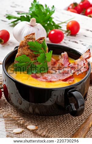 Cream of pumpkin soup with bacon and croutons - stock photo