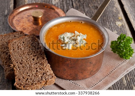 Cream of pumpkin soup with blue cheese, close up, horizontal - stock photo