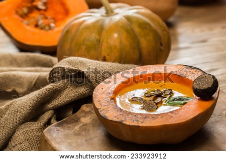 Cream of pumpkin soup with pumpkin seeds and and garlic croutons  in hollowed-out pumpkin. Shallow dof. - stock photo