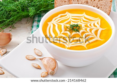 Cream of pumpkin soup with sour cream sauce - stock photo