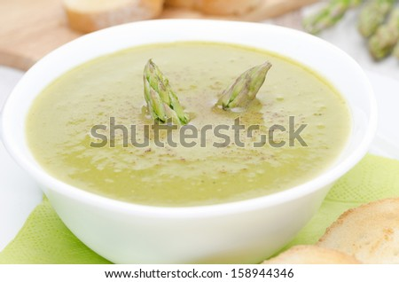 cream soup of asparagus and green peas  in a white bowl, close-up horizontal