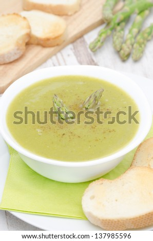 cream soup of asparagus and green peas in a white bowl vertical