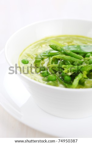 Cream soup with asparagus, peas and leeks in white plate - stock photo