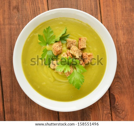 cream soup with crusts and green parsley - stock photo