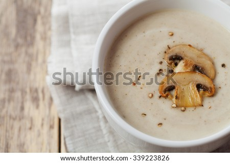 Cream soup with mushrooms champignon and potato in white bowl, vintage style - stock photo