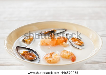 Cream-soup with shrimps and mussels copyspace. Bowl with seafood cream-soup on white wooden background. White soup with mussels and shrimps in bowl - stock photo