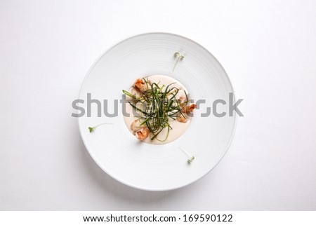 Cream soup with shrimps in a white round plate on a white background - stock photo