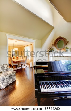 Cream yellow living room with grand piano and dining - stock photo
