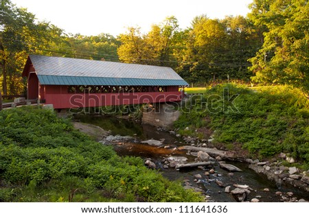 Creamery covered bridge built in 1879 in Brattleboro Vermont. Beautiful historic red covered bridge with a flowing stream of water below it. - stock photo