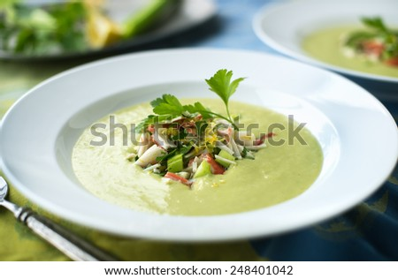 Creamy avocado soup with fresh crab salad - stock photo