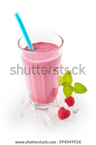 Creamy berry smoothie with fresh raspberries blended with yogurt served on ice with fresh fruit alongside isolated on white for a refreshing chilled drink - stock photo