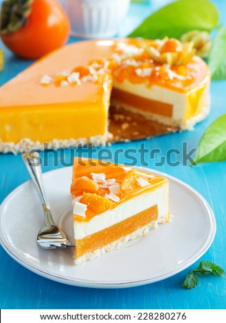 Creamy cake with coconut, mango and persimmon - stock photo