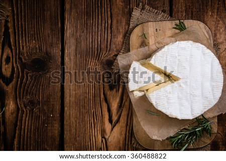 Creamy Camembert on rustic wooden background (detailed close-up shot) - stock photo