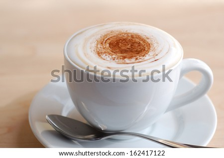 Creamy cappuccino on wooden surface with copy space. - stock photo