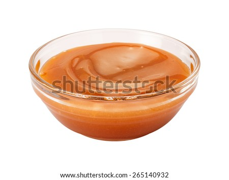 Creamy Caramel Syrup in a glass bowl. This sauce can be used for dipping, or as an ingredient. The image is a cut out, isolated on a white background, with a clipping path. - stock photo