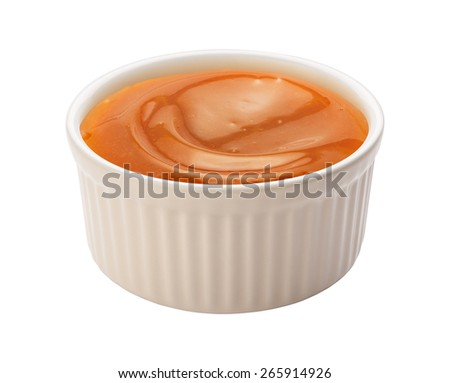 Creamy Caramel Syrup in a white ramekin. This sauce can be used for dipping, or as an ingredient. The image is a cut out, isolated on a white background, with a clipping path.