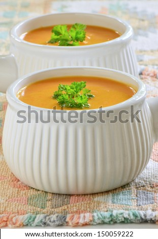 Creamy carrot and sweet potato soup with parley garnish in white ribbed soup bowls
