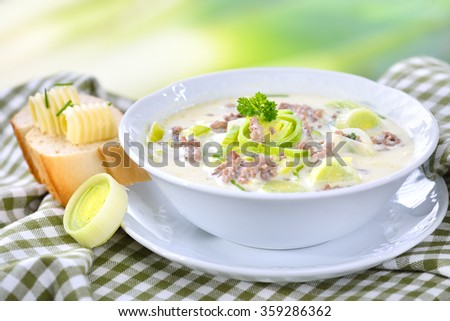 Creamy cheese and leek soup with minced meat, served with buttered ...
