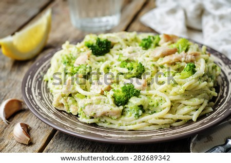 creamy cheesy broccoli spaghetti with chicken on a dark wood wood ...